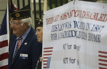 Veterans, including John L. Stamatiades, left, hold a banner at a news conference to announce a lawsuit against the federal government, alleging the misuse a 390-acre plot of land in West Los Angeles that was donated some 130 years ago to house veterans who need care after traumatic military experiences, at the Los Angeles Veterans Administration center in Los Angeles Wednesday, June 8, 2011. The suit alleges that the U.S. Department of Veterans Affairs leased much of the property at its West Los Angeles facility to private entities, instead of using it for veterans' permanent supportive housing. (AP Photo/Reed Saxon)